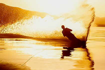 A waterskier carves a slalom turn on a glassy lake sending a spray of water across the setting sun.