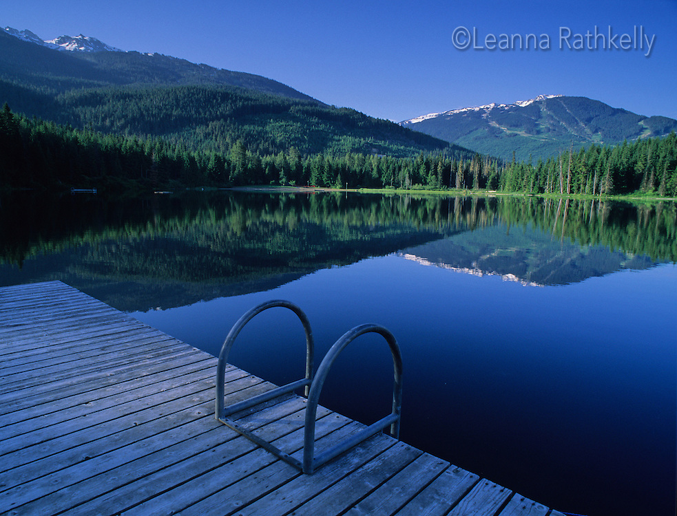 Lost Lake on an early summer morning, Whistler BC Canada reflects both Whistler (right) and Blackcomb (left) mountains.