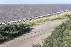 Road next to eroded railway line at Spurn Head; East Yorkshire; England; with Humber Estuary in background,
