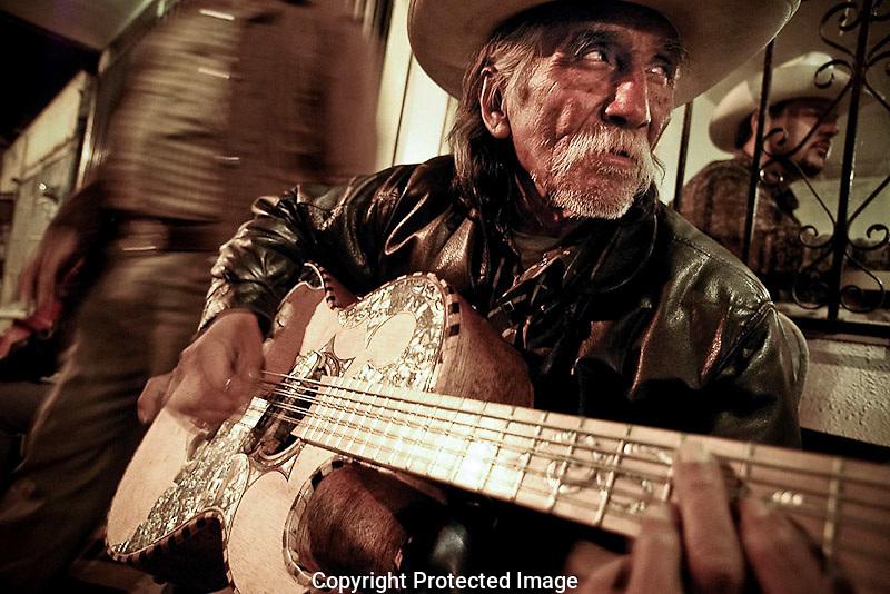 """Una figura típica en México es el músico callejero, en el norte los músicos de banda o música """"norteña"""" ofrecen su música en bares, cantinas y hasta a los autos. Un músico callejero conocido como """"el flaco"""" afina su guitarra afuera de un bar en el centro de Ensenada, aquí el pasa las noches esperando algún cliente que le pida alguna canción, también hace recorridos por los diferentes bares del centro de la ciudad ofreciendo su música."""