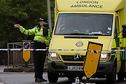 A WPC re-directs a London amubulance as a burst water main causes traffic havoc, closing Denmark Hill, weeks after the disastrous flooding in nearby Herne Hill, Denmark Hill was closed in both directions due to another burst water main in multiple locations across the road (A215) between the junctions of Champion Hill and Champion Park in south London. Water was seen running towards Kings College Hospital, 200 yards downhill and Denmark Hill is a major thoroughfare for the hospital's A+E.