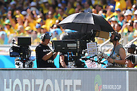 The television cameraman is covered by an umbrella to shade from the sun