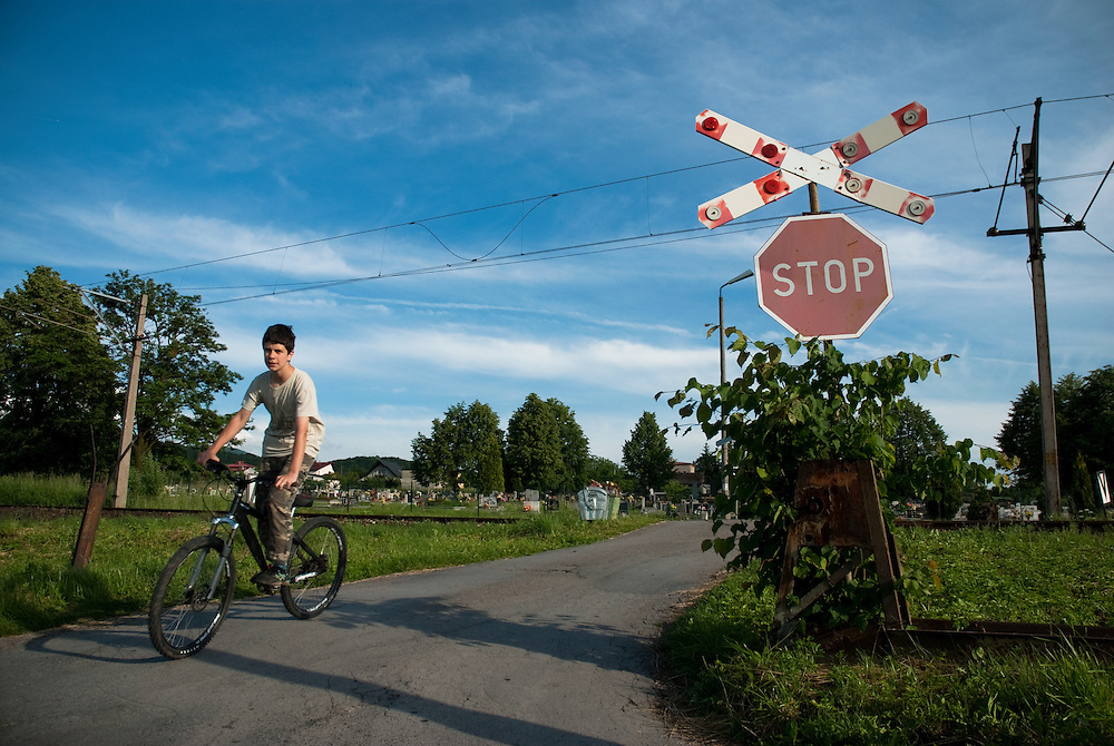 A boy cycling over a level crossing in the Beskidy mountains, Silesia, Poland. June 2009.