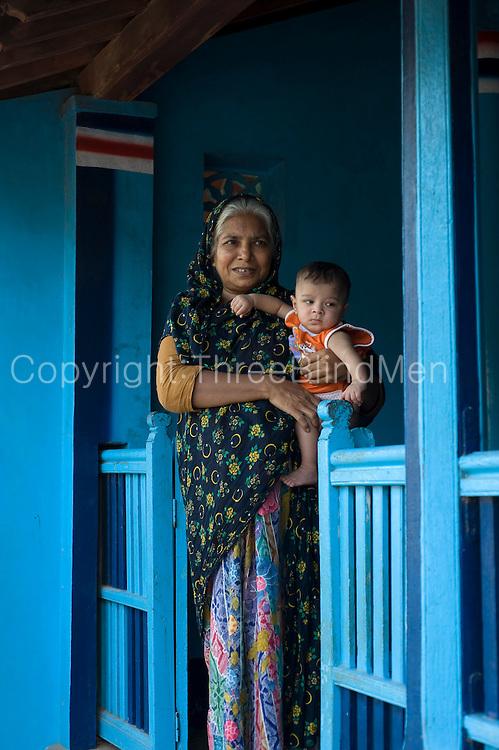Grandmother and grandson on veranda of their home. Thittacheri.<br /> Tamil Nadu. South India.