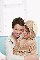 Mother and daughter (5-6) embracing and smiling girl in bunny costume