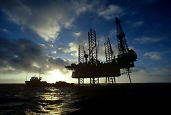 Jackup offshore oil drilling rig viewed from the water at sunrise.