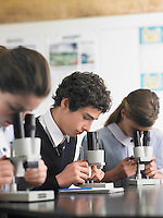 High school students using microscopes in classroom
