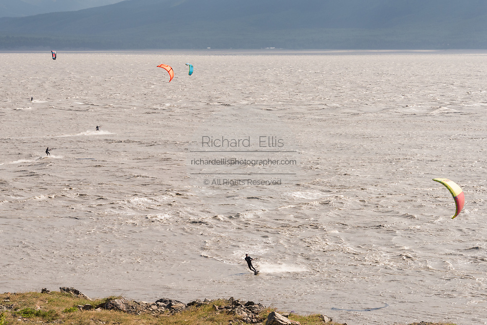 Kite surfers ride the bore tide past snow capped mountains on Turnagain Arm at Windy Point outside Anchorage, Alaska.