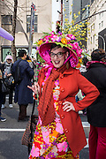 New York, NY, USA-27 March 2016. A woman in a flower print dress and an elaborate flower-covered hat in the annual Easter Bonnet Parade and Festival.
