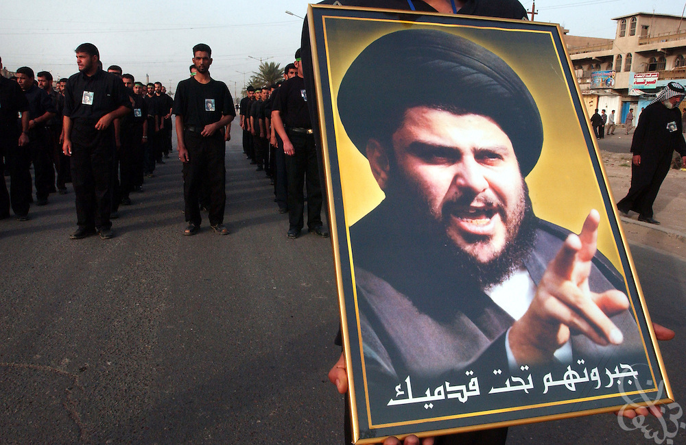 Members of the al-Mehdi Army  march in formation bearing a portrait of firebrand Shia cleric Moqtada Sadr during an April 03, 2004 military parade/show of force through the streets of the Sadr City neighborhood in east Baghdad, Iraq.