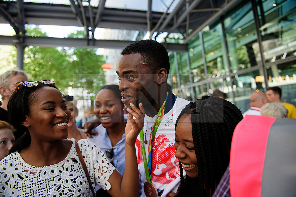 © Licensed to London News Pictures. 23/08/2016. London, UK. Olympic Bronze medal boxer Joshua Buatsi is greeted by family as he arrives at terminal 5 of London Heathrow Airport. Team GB finished second in the medals table with 67 medals, beating their total of 65 at London 202.  Photo credit: Ben Cawthra/LNP