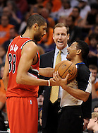 Nov. 21, 2012; Phoenix, AZ, USA; Portland Trail Blazers forward Nicolas Batum (88) talks with NBA Official Bill Kennedy (55) as head coach Terry Stotts watches on in the game against the Phoenix Suns in the first half at US Airways Center. Mandatory Credit: Jennifer Stewart-US PRESSWIRE.