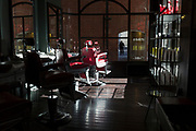 With the UK death toll reaching 38,161, a further 324 victims in the last 24hrs, and the government's pandemic lockdown still in effect, empty barbers' chairs remain empty in a closed hairdresser's in the City of London - the capital's financial district, on 29th May 2020, in London, England.