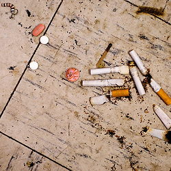 A pile of half-smoked cigarettes mixes with pills, a penny and an earring on the floor of a bathroom at a gas station.