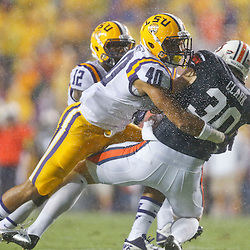 Sep 21, 2013; Baton Rouge, LA, USA; LSU Tigers linebacker Duke Riley (40) tackles Auburn Tigers punter Steven Clark (30) on a punt attempt during the first quarter of a game at Tiger Stadium. Mandatory Credit: Derick E. Hingle-USA TODAY Sports