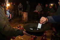 Romanian hunters participating in a lottery to share the freshly prepared meat of a female Wild boar (Sus scrofa) that was shot during a driving hunt. Mehadia, Caras Severin, Romania.