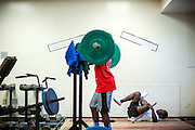 "BEAUFORT, SC - JULY 14: CJ Cummings, right, stretches his legs while the other students work out at the weight lifting facility at the Beaufort Middle School on July 14, 2014 in Beaufort, South Carolina. A former U.S. Olympic coach has called Cummings ""the best weightlifter this country has ever seen."" (Photo by Stephen B. Morton for The Washington Post)"