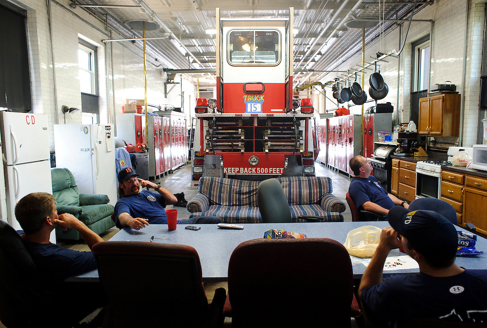 (photo by Matt Roth).Assignment ID: 30127696A.Wednesday, June 20, 2012..In between runs Baltimore City Truck 15 firefighters (L-R) EVD Keith Rider, EVD Chad Cowles, Lt. Lee Harper, and FF/PM Michael Sweeney watch a movie and eat in between runs Wednesday, June 20, 2012. After July 1st, this company's members will be disbanded to other companies and the company's truck (their's is being repaired. The one they're using is a reserve truck) will be used as a reserve...City Councilman William Pete Welch proposes advertisements be allowed on Baltimore City Fire Department vehicles as a way to combat a $48 million budget shortfall, rather than disbanding three companies, including Truck Company 15, which services East Baltimore.