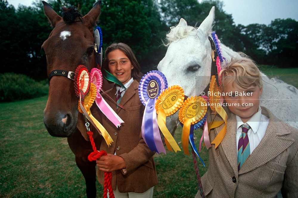 "Two young 1990s girls stand with their beloved ponies at a gymkhana in, on 17th September 1999, in Cheltenham, Gloucestershire, England. The word gymkhana is an Indian Raj term which originally referred to a place where sporting events took place and referred to any of various meets at which contests were held to test the skill of the competitors. In the UK and east coast of the US, the term gymkhana now almost always refers to an equestrian event for riders on horses, often with the emphasis on children's participation (such as those organised here by the Pony Club). Gymkhana classes include timed speed events such as barrel racing, keyhole, keg race (also known as ""down and back""), flag race, and pole bending. (Photo by Richard Baker / In Pictures via Getty Images)"