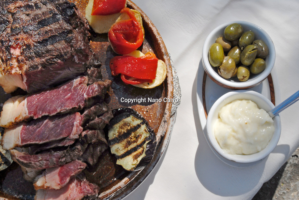 Grilled meat, olives, ali oli and other traditional ibizan food in popular Es Caliu restaurant, Ibiza, Spain