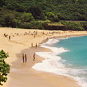 Bathers and sun worshippers on famed Sunset Beach on Oahu's North Shore in Hawaii.