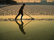 10 FEBRUARY 2016 - BAN LAEM, PHETCHABURI, THAILAND: A worker rakes up salt in a salt field at the beginning of the harvest in Phetchaburi province, Thailand. The salt harvest in Thailand usually starts in February and continues through May. Salt is harvested in many of the provinces along the coast, but the salt fields in Phetchaburi province are considered the most productive. The salt fields are flooded with sea water, which evaporates off leaving salt behind. Salt production relies on dry weather and producers are hoping the current drought will mean a longer harvest season for them.      PHOTO BY JACK KURTZ