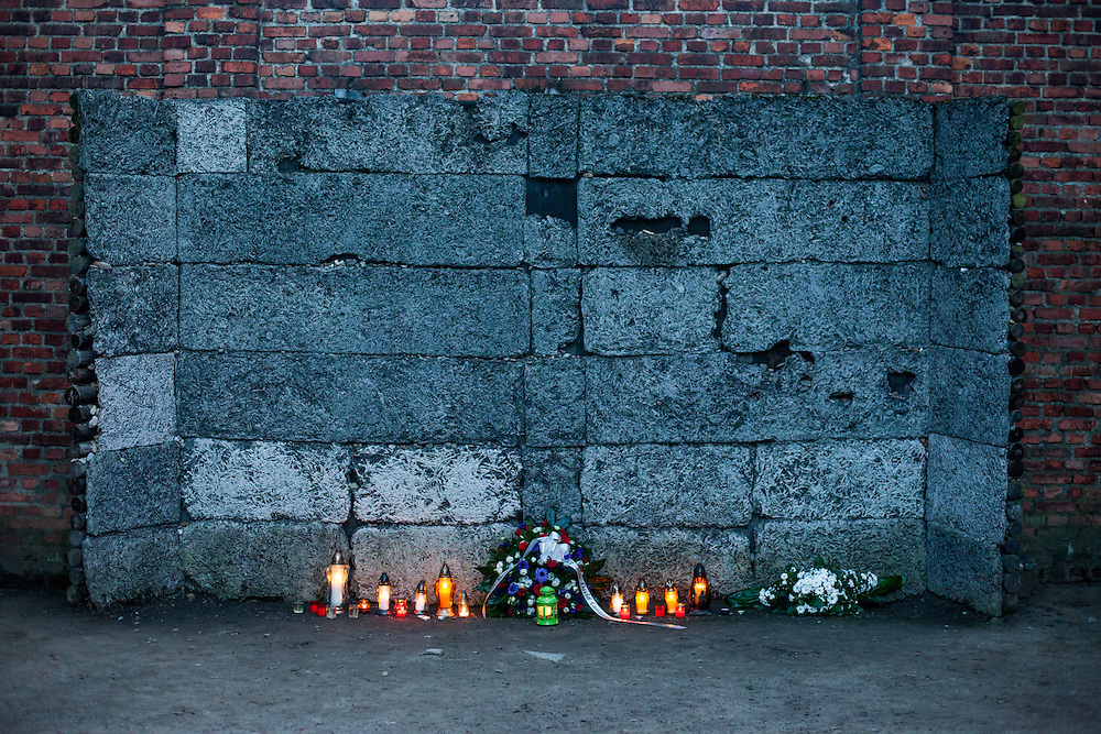 Candles and flowers by British PM David Cameron at the Death Wall (BlackWall) where shooting executions took place at the Auschwitz Nazi concentration camp. It is estimated that between 1.1 and 1.5 million Jews, Poles, Roma and others were killed in Auschwitz during the Holocaust in between 1940-1945.