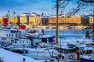 Skutor vid kajen på Skeppsholmen i Stockholm en solig vinterdag