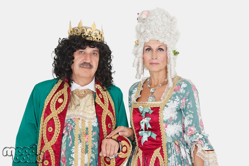 Portrait of senior king and queen standing over gray background