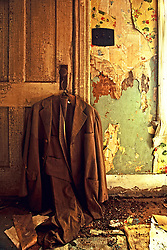 An old suit coat hanging on the front door knob in an abandoned farm house in SE Minnesota