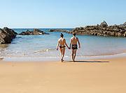 Couple holding hands on beach walking into sea, Praia dos Alterinhos, Zambujeira do Mar,  Portugal, Southern Europe