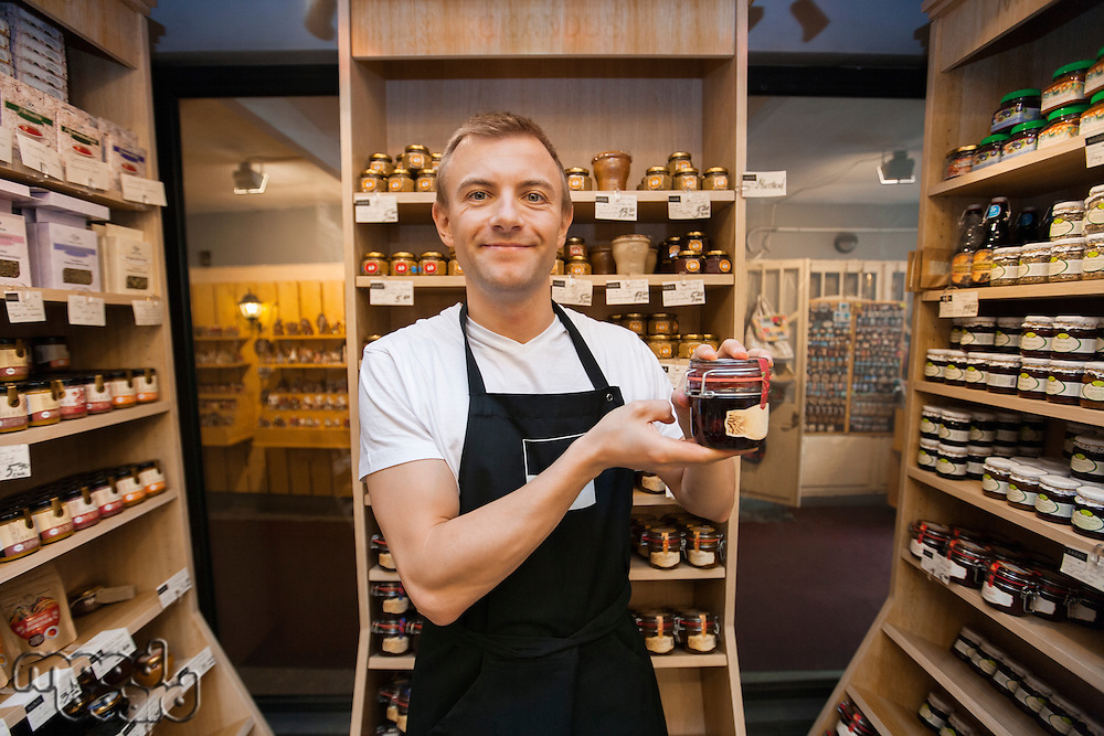 Portrait of mid adult salesman holding jar of jam in grocery store