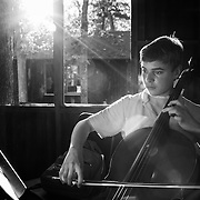 Alex Shier, 13, of Michigan, plays his cello while in the practice huts at Interlochen Center for the Arts in Interlochen, Michigan.