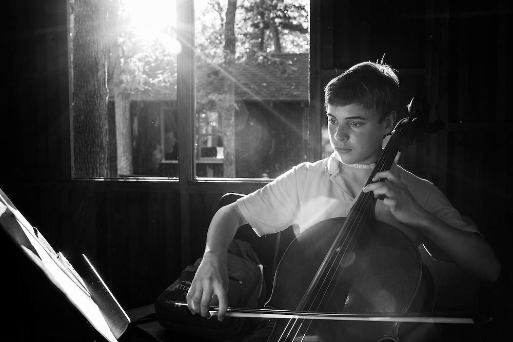 Alex Shier, 13, of Michigan, plays his cello while in the practice huts at Interlochen Center for the Arts in Interlochen, Michigan.