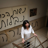 "Peggy Cidor, a leading woman of the Women of the Wall organization, stand in the hallway of her building in Jerusalem, Monday, May 20, 2013. The grafitti reads"" The women of the Western Wall are despised"". The group, known as ""Women of the Wall,"" convenes monthly prayer services at the Western Wall, the holiest site where Jews can pray, wearing prayer shawls and performing rituals that ultra-Orthodox Jews believe only men are allowed to do...Israeli officials initially opposed the group but have recently backed its right to worship. Earlier this month, thousands of ultra-Orthodox protesters tried to prevent their prayer service"