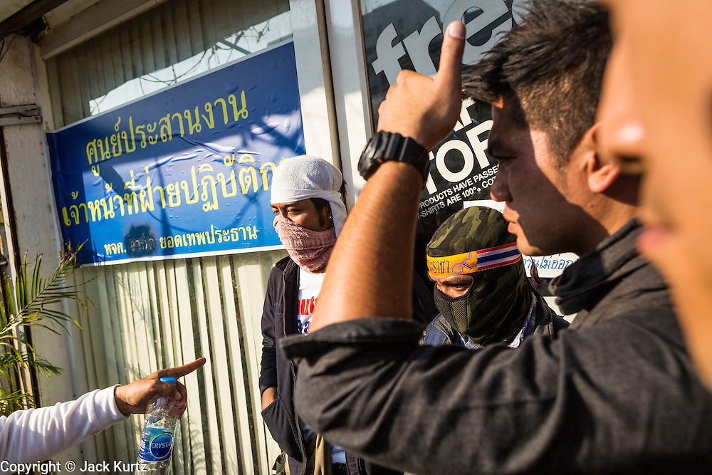 17 JANUARY 2014 - BANGKOK, THAILAND: Anti-government protestors guard the door to an abandoned building they believe was used to plan an IED attack on one of their marches Friday. The attackers were not found but officials claim to have found a weapons cache in an abandoned building nearby. Friday was day 5 of the anti-government Shutdown Bangkok protests. The protest, led by the People's Democratic Reform Committee, is calling for the suspension of elections pending political reform in Thailand. There was violence at several sites in Bangkok Friday, including running battles between government opponents and supporters at one site and an IED attack by unknown assailants on anti-government protestors at another site.    PHOTO BY JACK KURTZ