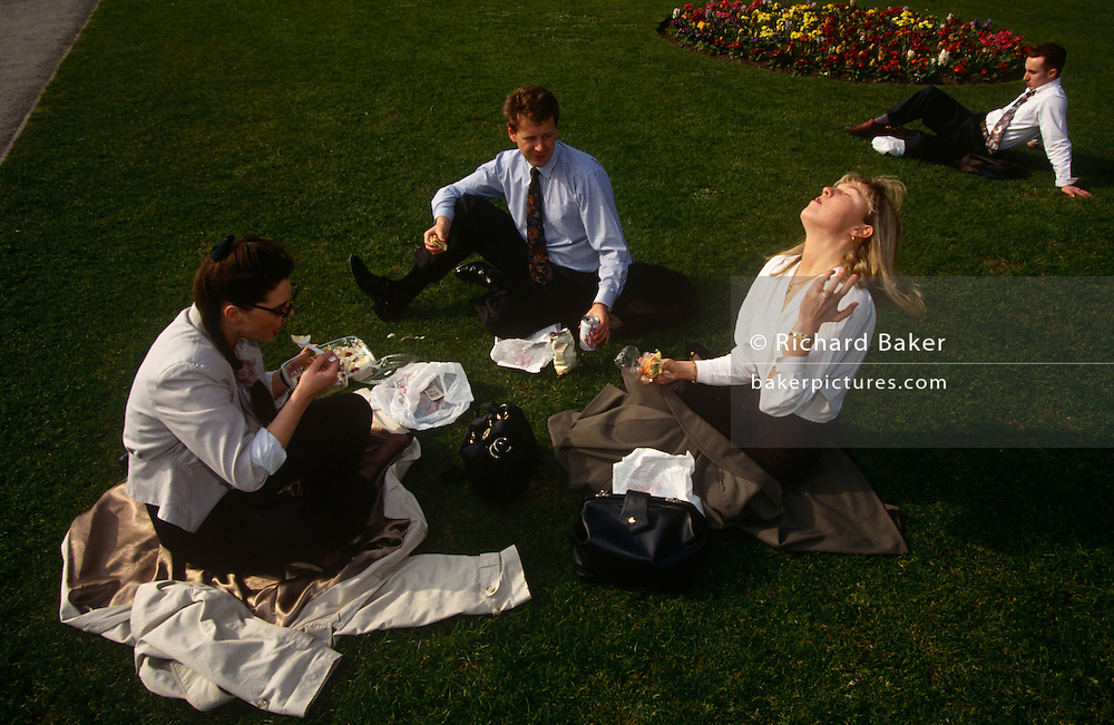 Three work colleagues enjoy a picnic on the grass in a City of London park in summer sunshine.