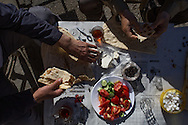 Two men sit down to a simple breakfast of fresh cheese, olives, cucumber and tomato in Diyabakir, Turkey