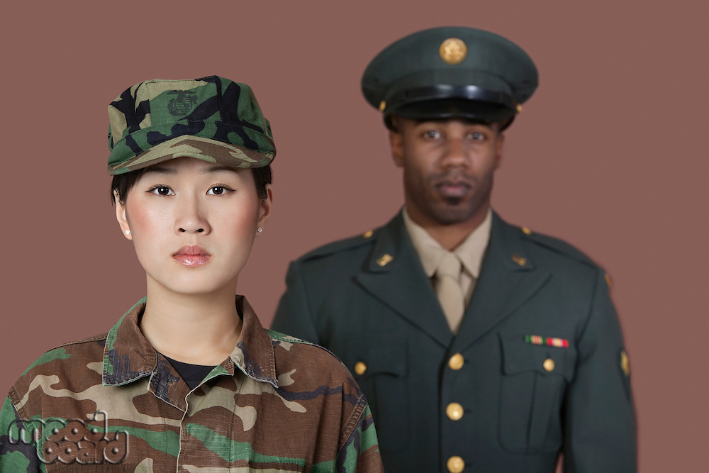 Portrait of young female US Marine Corps soldier with male officer in background