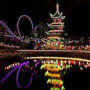 Lights and reflections at night at a Chinese pagoda restaurant at Tivoli Gardens in Copenhagen, one of the oldest amusement parks in the world.