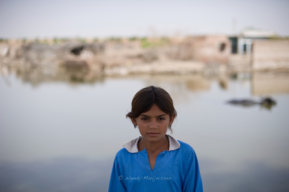A girl stands in front of her former home flooded by water. One month after the devastating monsoon rains caused huge floods in Pakistan, new areas are still affected and water still stands among fields and houses. Jamshoro, Pakistan, 2010
