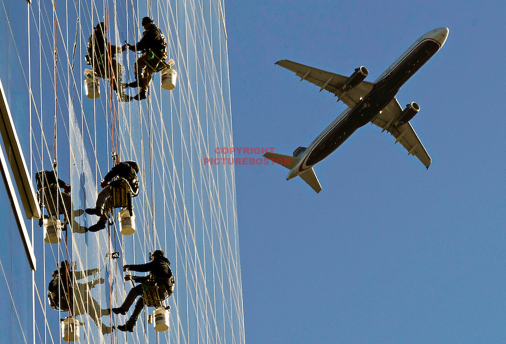 11/13/2013-Boston,MA.  Window washers on Northern Ave. are framed by a departing Logan airport jet.