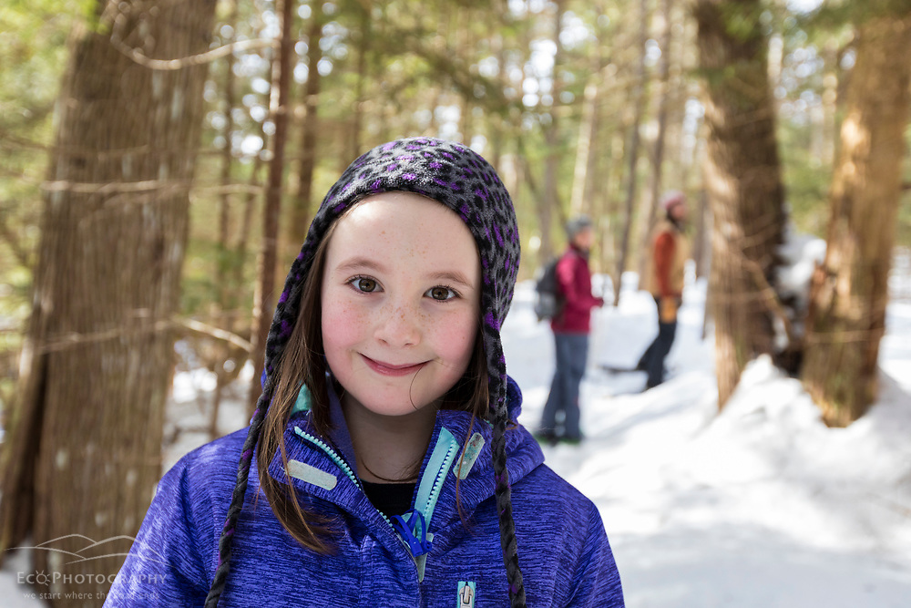 A girl snowshoeing with her parents on the Upper Works Trail, Tahawus Tract, Newcomb, New York. Adirondack Mountains.
