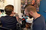 Garden City, New York, USA. September 13, 2015. R-L, GUNNAR VALDIMARSSON, from Akureyri, Iceland, is tattooing the arm of his brother KRISTJAN VALDIMARSSON, at the United Ink Flight 915 Tattoo convention at the Cradle of Aviation Museum in Long Island. The brothers are from Iceland, and the tattoo has a Nordic Viking theme.