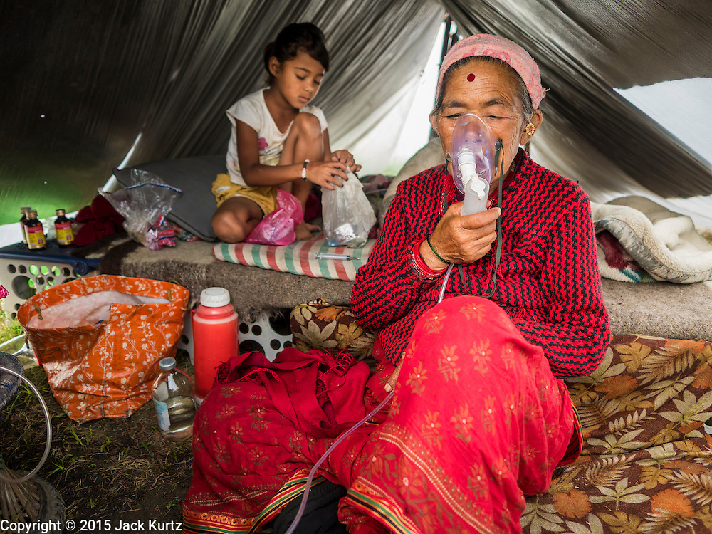 05 AUGUST 2015 - KATHMANDU, NEPAL: With her granddaughter watching her in their tent. CHANDRA MAYA SUNAR, 57 years old, breathes through an oxygen mask in a large Internal Displaced Person (IDP) Camp in the center of Kathmandu. She came to Kathmandu with her family from Sindupalchok after the earthquake. The camp is next to one the most expensive international hotels in Kathmandu. More than 7,100 people displaced by the Nepal earthquake in April live in 1,800 tents spread across the space of three football fields. There is no electricity in the camp. International NGOs provide water and dug latrines on the edge of the camp but the domestic waste water, from people doing laundry or dishes, runs between the tents. Most of the ground in the camp is muddy from the running water and frequent rain. Most of the camp's residents come from the mountains in northern Nepal, 8 - 12 hours from Kathmandu. The residents don't get rations or food assistance so every day many of them walk the streets of Kathmandu looking for day work.     PHOTO BY JACK KURTZ