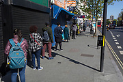At the beginning of the fourth week of the UK government's lockdown during the Coronavirus pandemic, and with 120,067 UK reported cases with 16,060 deaths, a local bank users practice social distancing in a queue for the Natwest Bank in Camberwell in South London, on 20th April 2020, in London, England.