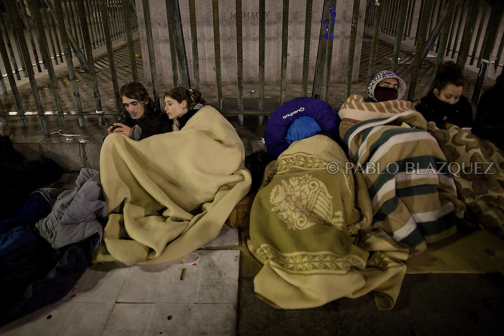 Demonstrators cover themselves with blankets on the first night of a camp protest in Puerta del Sol Square after a demonstration against alleged corruption scandals implicating the PP (Popular Party) on February 4, 2013 in Madrid, Spain. Spain's Prime Minister Mariano Rajoy yesterday denied receiving undeclared payments from his political party. More information on secret payments were revealed today and leader of opposition socialist Party (PSOE) urged Rajoy to resign.