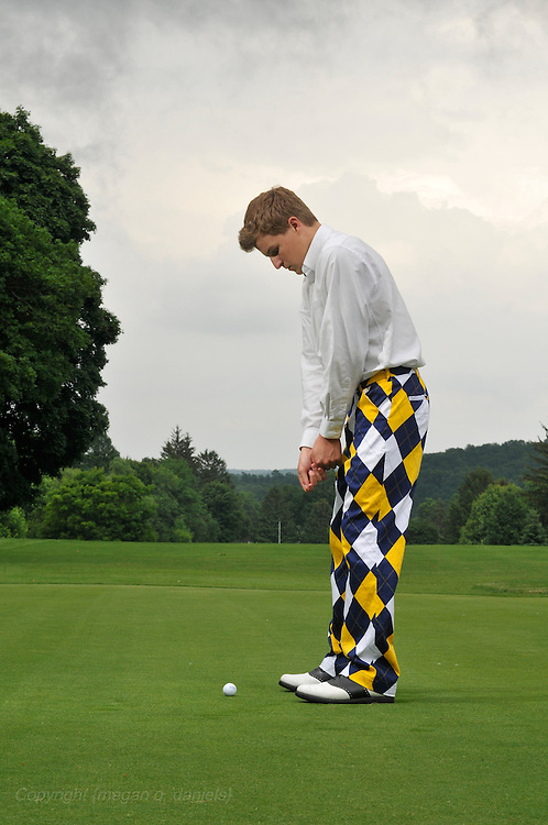 17-year-old Zach Daniels, a Caucasian male, poses for his senior portraits in Ithaca NY. He is wearing a suit in an alley and while standing in a barn window, jeans and a gray t-shirt sitting near license plates, blue and yellow argyle pants on a tee at a golf course in Cortland, NY.
