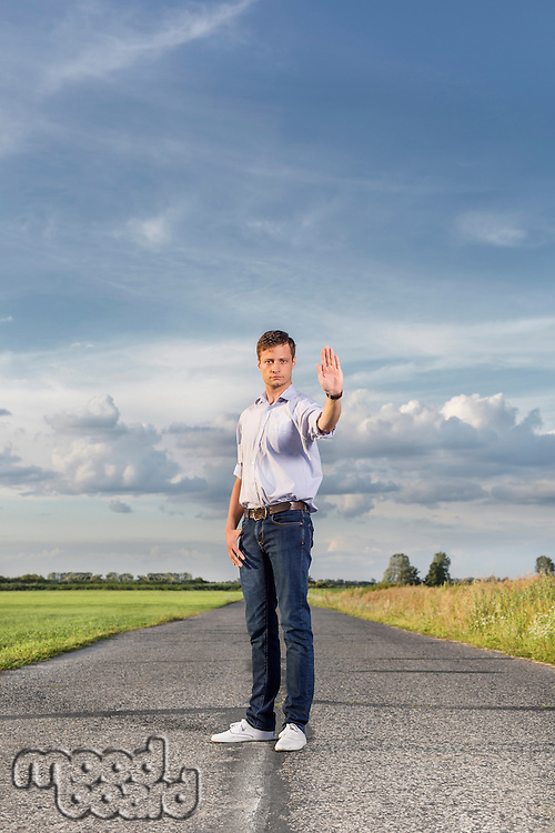 Full length of serious young man holding up hand to stop at country road