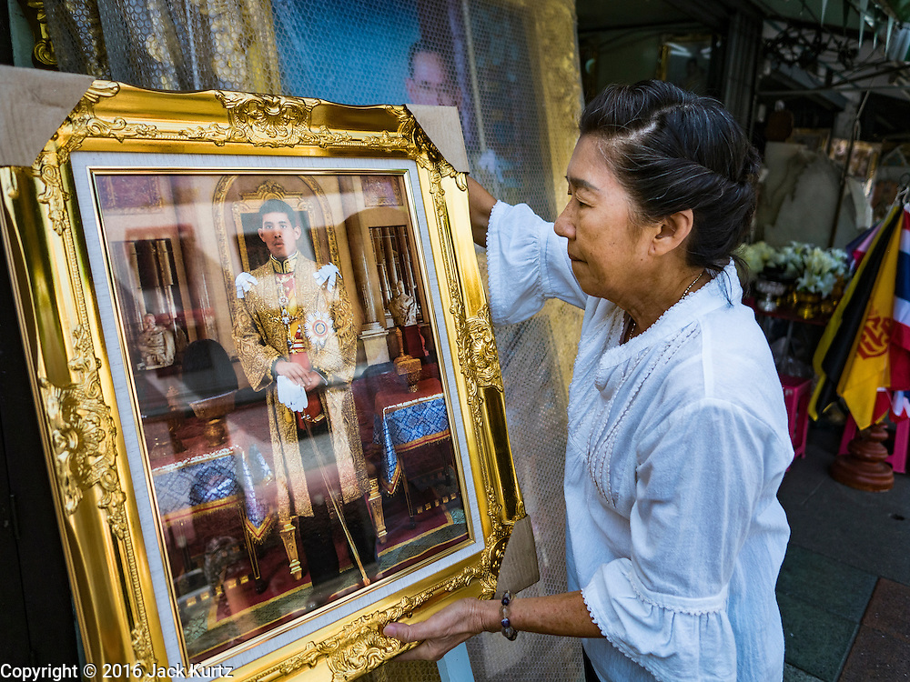 01 DECEMBER 2016 - BANGKOK, THAILAND:  A shopkeeper sets out a portrait of Crown Prince Vajiralongkorn, who will soon be the new King of Thailand. Thailand's parliamentary body, the National Legislative Assembly, invited HRH Crown Prince Maha Vajiralongkorn to be king following the death of the Crown Prince's father, Bhumibol Adulyadej, the Late King of Thailand. The invitation marked the formal beginning of the process of naming the new King, although Crown Prince Vajiralongkorn was the heir apparent and Bhumibol's appointed successor. Shops that sell royal paraphernalia are now selling new portraits of  Crown Prince Vajiralongkorn which will be displayed alongside portraits of his late father. King Bhumipol died on Oct 13.     PHOTO BY JACK KURTZ